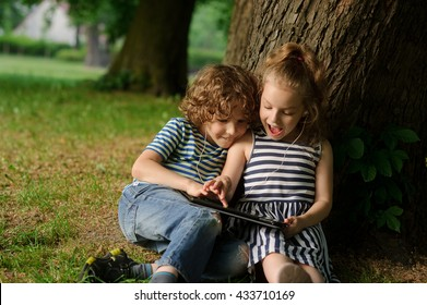 Brother with sister of 7-9 years sit under a tree and look in the laptop.Children sit having leaned against a trunk of a old tree and with enthusiasm look at the screen.They have one earphones for two