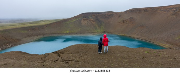 Brother and sister admiring the Volcano Viti Crater in North Iceland near Myvatn Lake