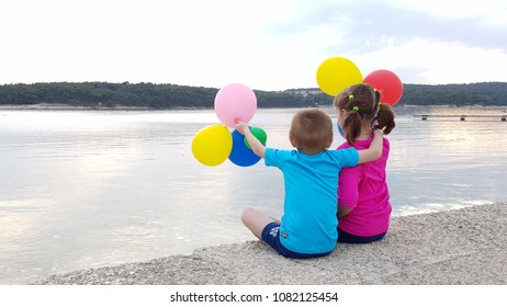 brother and sister with balloons on the sea
