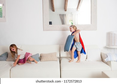 Brother and sister children playing on home living room couch wearing fancy dresses, having fun with energetic games, indoors. Family relatives enjoying time together, kids lifestyle.