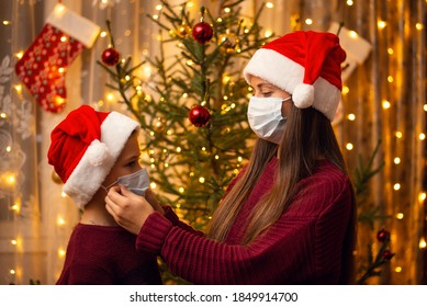 Brother and sister in christmas hats, burgundy sweaters and medical masks stand near decorated fir-tree. Family together, holidays, New Year's preparations during lockdown.