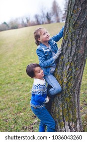 brother and sister climbing tree