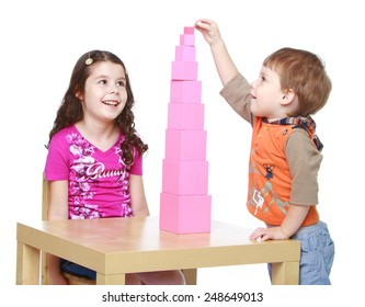 Brother and sister collects Red Pyramid in the Montessori kindergarten.Isolated on white background, Lotus Children's Center