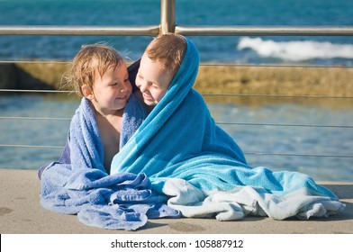 Brother and sister cuddling in a towel after a swim at the beach