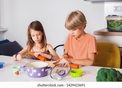 Brother and sister cutting vegetables,kids helping in the kitchen,healthy life concept