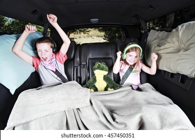 A Brother and Sister Dancing in the back of a Car