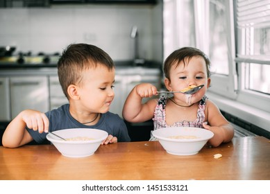 Brother and sister eat cornflakes with milk in the kitchen during the day very fun and cute, dirty and funny ones