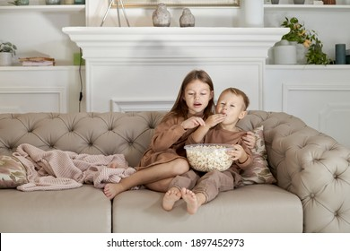 Brother and sister eating popcorn sitting at home on the couch. A boy and a girl relax have fun and watch a movie on TV