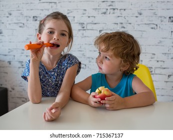 brother and sister eating vegetables and fruits