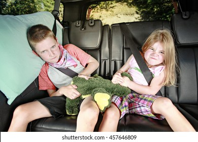 Brother and sister fighting in the back of a car