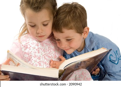 brother and sister having fun with a book