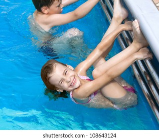 brother sister having fun doing exercises in pool