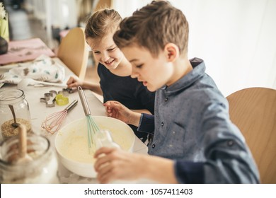 brother and sister having fun while baking cookies in the kitchen