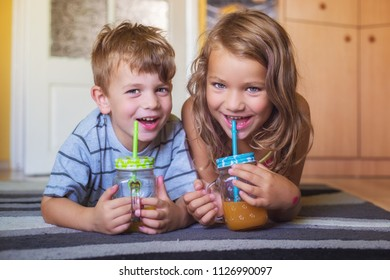 Brother and sister having fun while sipping juice at home