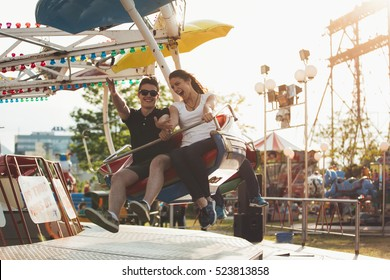 Brother and sister having a ride at an amusement park. Spending free time together. Bonding and entertainment concept.Beautiful sunset at theme park in summer holiday vacation.