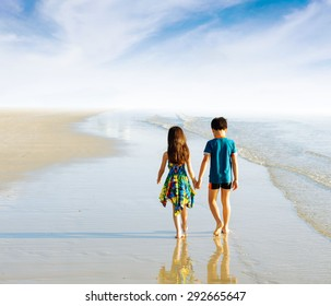 Brother sister holding hand walk on the beach in tropical seaside under blue sky white cloud
