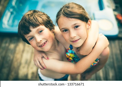 Brother and sister hugging in bathing suit in front of a jacuzzi