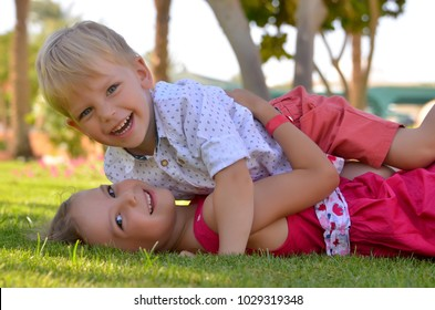 Brother and sister hugging and playing on grass in a park on a summer sunny day
