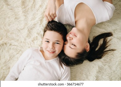 Brother and sister hugging and smiling, lying on the floor