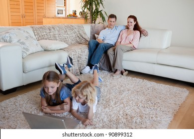 Brother and sister with laptop on the living room carpet