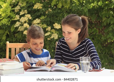 Brother and sister learning together in the garden.
