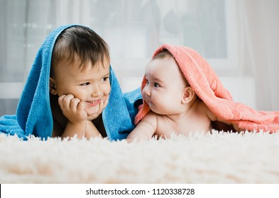 Brother and sister lie with towels on their heads, family love, younger and older