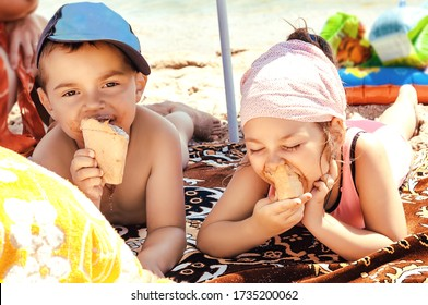 Brother and sister, little children are lying on the beach and eating ice cream.