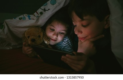 Brother and sister lying on the bed looking at the tablet in the dark