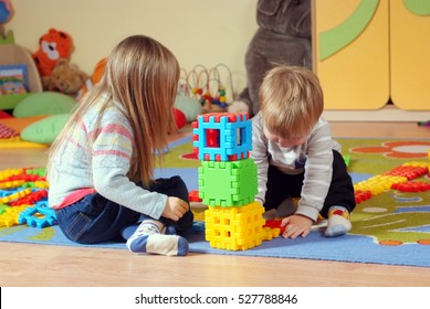 Brother and sister lying on the carpet, arranges towers with blocks