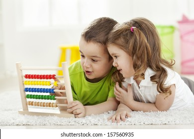 Brother and sister lying  on the floor with abacus, having fun