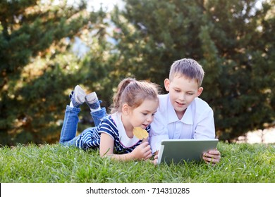 Brother and sister lying on the grass in the park and play tablet. Children watch cartoons on the tablet.