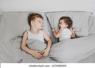 Brother and sister morning concept. Little boy look to his sister girl in the bed and smiles to each other after waking up. They are wearing white t-shirts