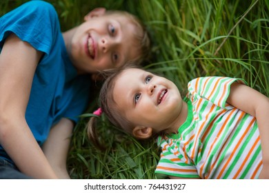Brother and sister in nature, Two children lie on the grass in summer