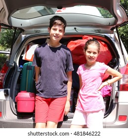 brother and sister near the trunk of the car before leaving with family
