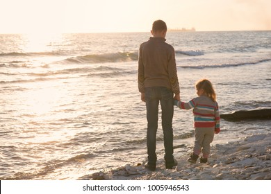 Brother and sister on the beach at sunset, Two children in nature