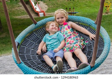 brother and sister on giant swing in playground