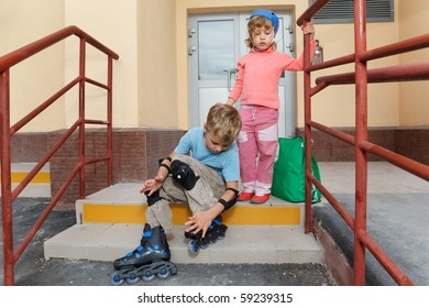 Brother and sister on steps of house. Boy in roller skates, elbow and knee caps.