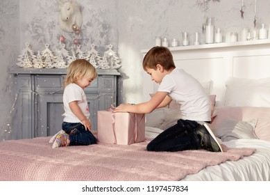 Brother and sister opening the Christmas gift sitting on the bed. The New Year holiday.