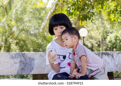 Brother, sister Play phone in park