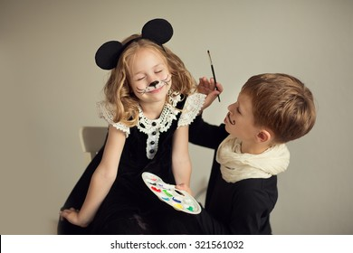 Brother and sister playing at artist and model. Face painting,