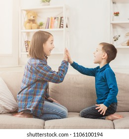 Brother and sister playing clapping hands together at home. Children game, joint activities and interests, trust, support, entertainment concept