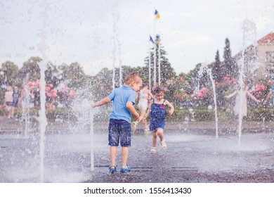 Brother and sister are playing in a fountain