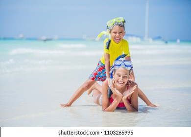 Brother and sister playing and having fun on the beach during the hot summer vacation day.