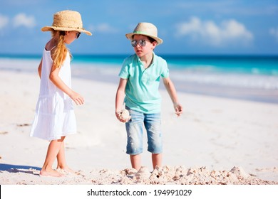 Brother and sister playing and having fun at beach on summer vacation