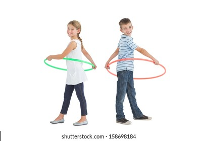 Brother and sister playing with hula hoop together on white background