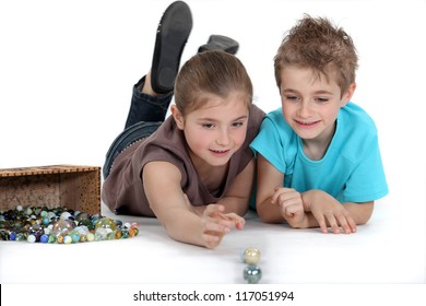 brother and sister playing marbles together