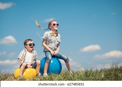 Brother and sister playing on the field at the day time. Children having fun outdoors. They jumping on inflatable balls on the lawn. Concept of friendly family.