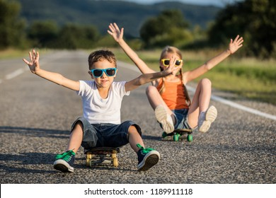 Brother and sister playing on the road at the day time. Children having fun outdoors. They skateboarding on the road. Concept of friendly family.