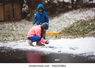 Brother and sister playing outside in the snow