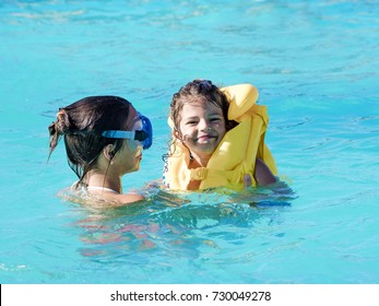 Brother and sister playing in the swimming pool at the day time. People having fun outdoors. Concept of happy family.